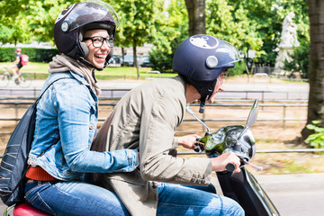 Young woman with helmet sitting on pillion seat of Vespa in streets of Berlin