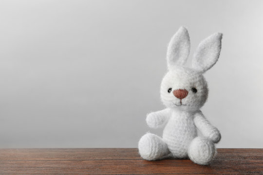 Cute knitted bunny toy on table against light background