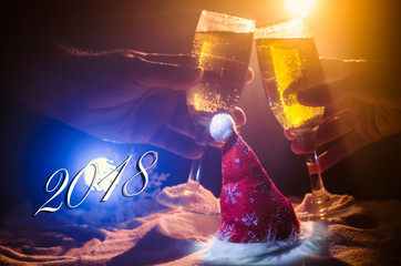 New Year Eve celebration background with pair of flutes and bottle of champagne with Christmas attributes (or elements) on snowy dark toned foggy background. Selective focus.