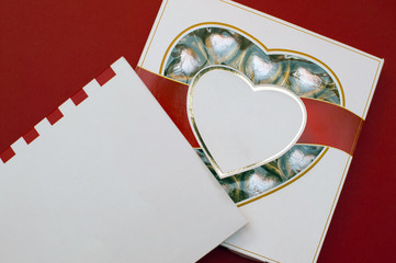 Beautiful love concept for Valentines day. Romantic box of sweets and modern note book on the red background.