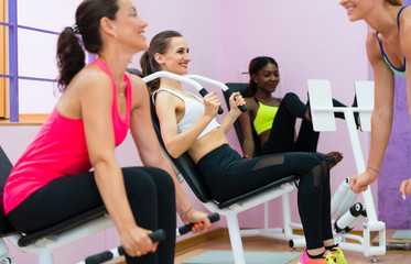 Side view of a brunette woman smiling while using modern equipment for toned arms during interval workout supervised by a qualified female instructor