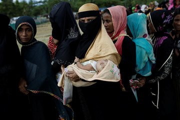 A woman holds her baby as Rohingya refugees wait for food supplies to be distributed at the Nayapara camp near Cox's Bazar