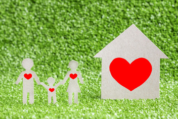 house model and family with red heart. family love concept, on green grass background. Valentine's Day