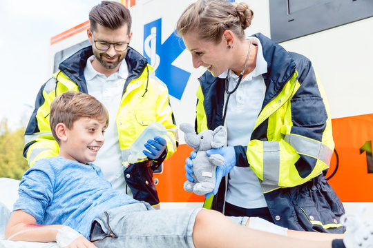 Emergency medic giving soft toy to console injured boy, with success