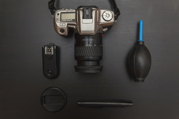 top view of work space photographer with dslr camera system, camera cleaning kit and camera accessory on black table background