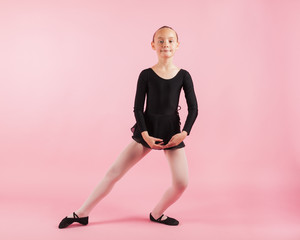 Portrait of young beautiful child girl ballerina standing practicing ballet wearing black tutu dress posing in studio with light pink background.