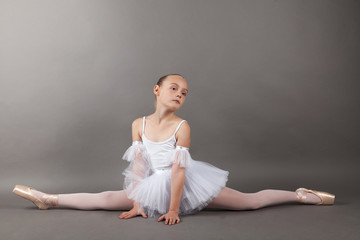 Young beautiful child girl ballerina doing split practicing ballet wearing white tutu dress on light gray background. Samakonasana stretching exercise, straight angle pose.