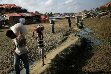 Rohingya refugees carry supplies at the Mayner Ghona camp near Cox's Bazar