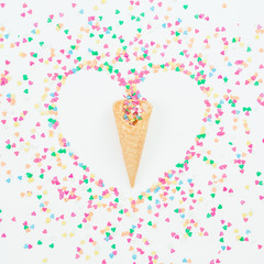 Heart made of bright candy confetti and waffle cone on white background. Flat lay, top view copy space. Love concept