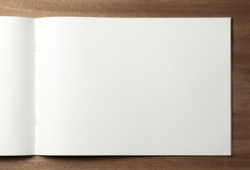 Empty sheet of sketchbook or album for drawing on wooden background.