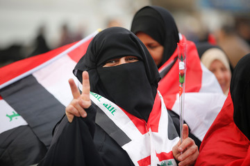 An Iraqi woman flashes a victory sign as she celebrates the final victory over the Islamic State at Tahrir Square in Baghdad