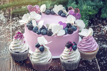 Purple beautiful cake decorated with berries, blackberries and blueberries on top with cupcakes on the festive table