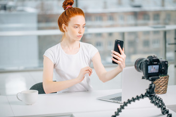 Young female redhead blogger with laptop recording video at home and take selfie.