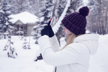 girl in a winter forest with a fashionable modern mobile phone (smartphone) in special gloves for working with a touch screen