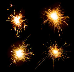 Bright sparks on deep black background closeup. Set of party holiday sparklers isolated on black