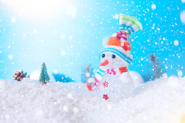 Cute snowman in the snow over blue wooden background