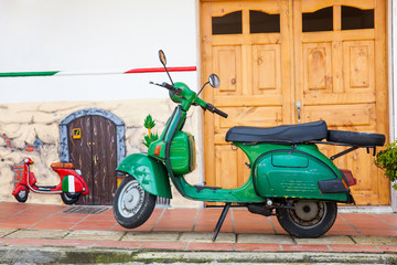 Scooter Green motorcycle at the colorful town of Guatape, Antioquia – Colombia.