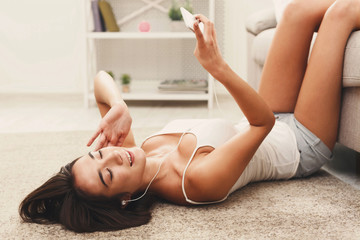 Happy girl enjoying her favorite song in earphones