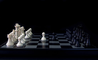 White pawn and black pawn on chess table. Black chess set in order for game start.