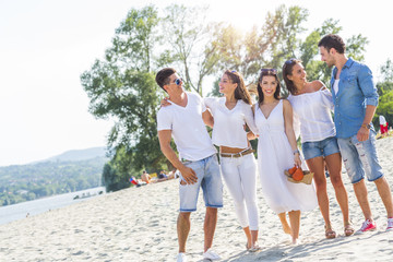 Group of young people holding hands on beach