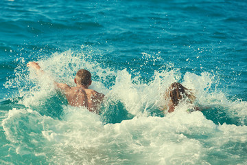 Caucasian couple running into the sea water. Back view.