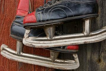 старые цветные коньки висят на деревянной стене