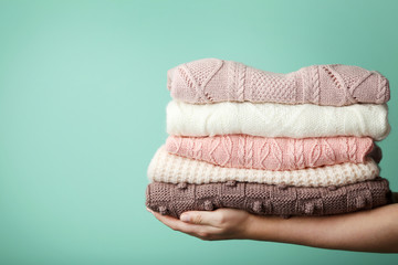 Female hands holding stack of knitted sweaters