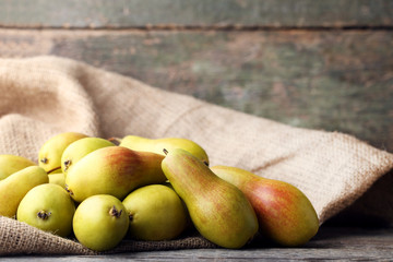 Ripe and sweet pears with sackcloth on grey wooden table