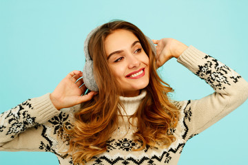 Pretty young woman in warm sweater over blue background