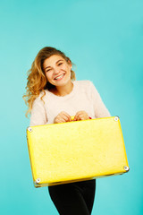 Young happy beautiful woman holding yellow suitcase over blue background
