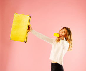Young happy woman holding empty credit card in one hand and yellow suitcase in another over pink background
