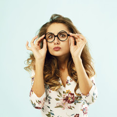 Beautiful attractive woman in round glasses over blue background