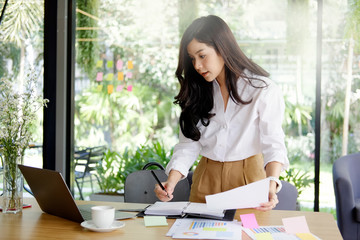 Businesswoman standing at her desk and working document paper with laptop.