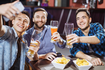 Handsome friends are drinking beer, doing selfie and smiling while resting in pub.