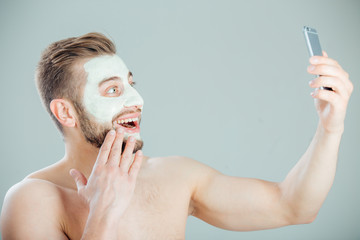 Young and beautiful man with Purifying Mask on his face doing selfie.