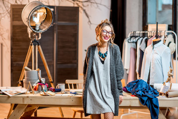 Portrait of a young female fashion designer standing at the office with different tailoring tools and clothes Wall mural