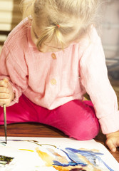 The child draws a picture with pencils