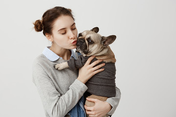 Nice shot of adult girl kissing cute small dog while holding it with tenderness. Portrait of dog and its female owner cuddling spending time together being friends. Display of affection