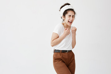 Lucky female with curly bushy hair in bun in white t-shirt keeping fists clenched opening her mouth and closing eyes with pleasure feeling great excitement and triumph isolated against white wall