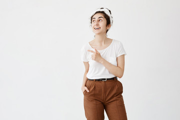 Smiling woman with dark wavy hair in bun in casual clothes posing against white studio wall pointing at copy space for your advertisment or text. Positive girl with hair bun advertising something