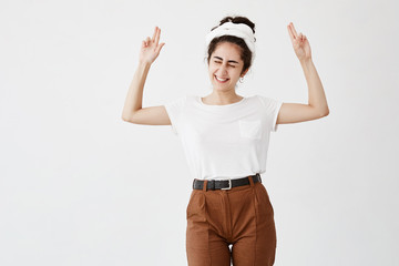 Excited overjoyed dark-haired woman points at copy space, closing her eyes, smiles broadly, advertisizes. Happy female in white t-shirt poses against white wall with copy area for promotional text