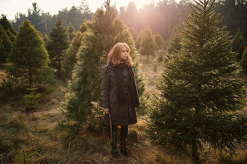 Sad Woman stands with Christmas trees while Holding a hand saw