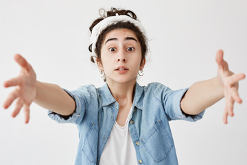 Pretty girl with wide opened eyes wearing do-rag and denim shirt asking for something, stretching her arms to camera to get what she wants. Cute dark-haired young poses against white blank wall