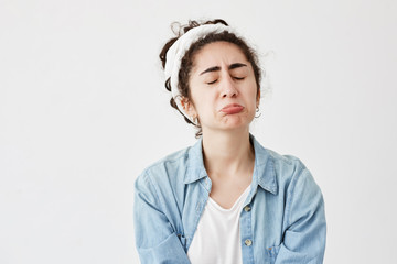Miserable upset gloomy female with dark and wavy hair looks offended, pouts lips, frowns face in dispair, frustrated, after receiving bad news. Unhappy young girl in denim shirt cries in frustration
