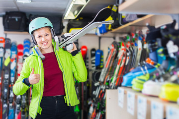 woman in jacket and helmet is demonstraiting ski in shop.