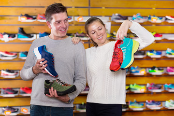 Girl and guy choosing clothes and shoes for sports