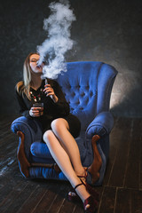 Woman vaping fumes and drinking alcohol to relax. Enjoyment satisfaction and chilling concept