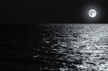 Fotomurais - moonlight on the waves at night in the sea on long exposures. black and white photo.