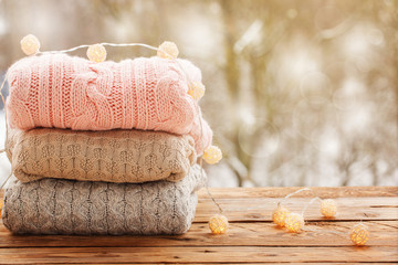 Cozy pile of knitted sweaters on wooden table on winter nature background with snow
