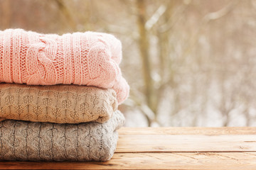 Cozy pile of knitted sweaters on wooden table on winter nature background.